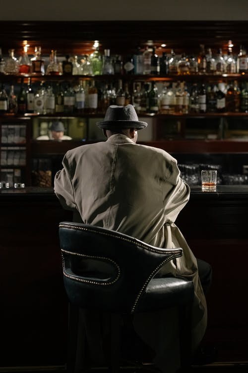 Photo of Person Sitting in Front of Bar Counter
