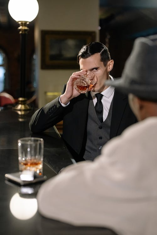 Photo of Man in Black Suit Holding Clear Drinking Glass
