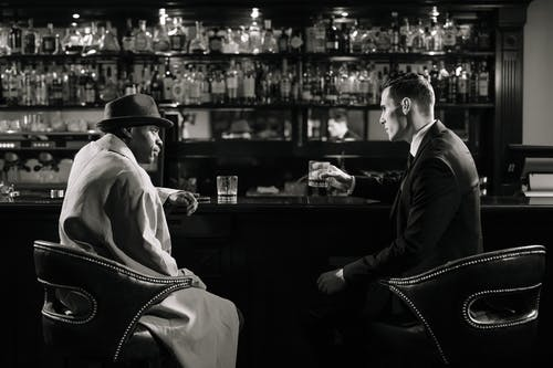 Monochrome Photo of Men Sitting in Front of Bar Counter