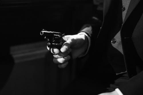 Grayscale Photo of Person Holding Black Revolver Pistol
