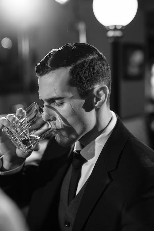 Monochrome Photo of Man Drinking Whiskey