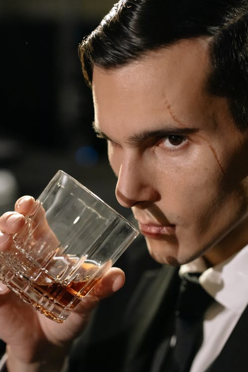 Close-Up Photo of Man Holding Glass of Whiskey