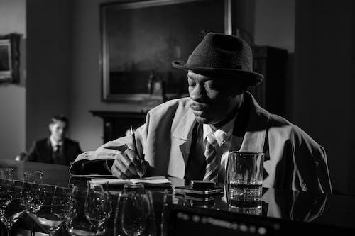 Monochrome Photo of Man Taking Notes