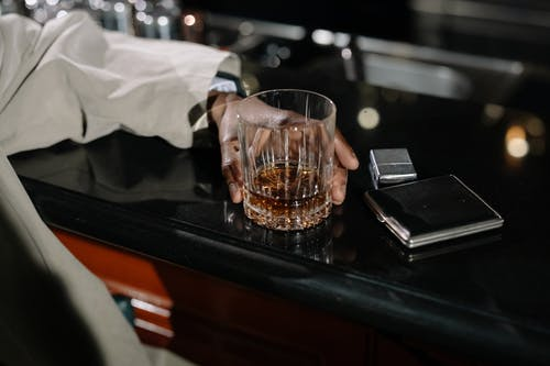Close-Up Photo of Person Holding Glass of Whiskey