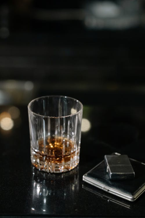 Photo of Clear Glass with Whiskey on Counter Top