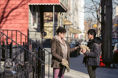 Adult sportswomen in activewear and warm clothes sharing towels and water bottles while standing on sunny autumn street