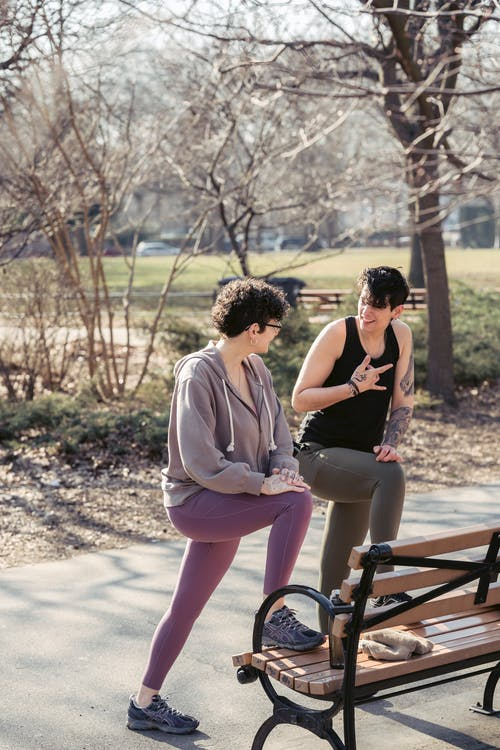 Full body content adult sportswomen stretching legs on bench and chatting while warming up in sunny autumn park together