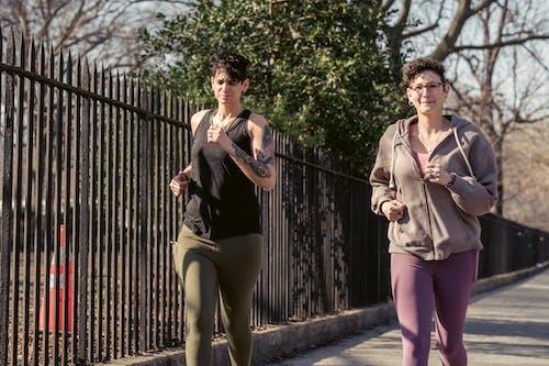 Adult sportswomen jogging together on street