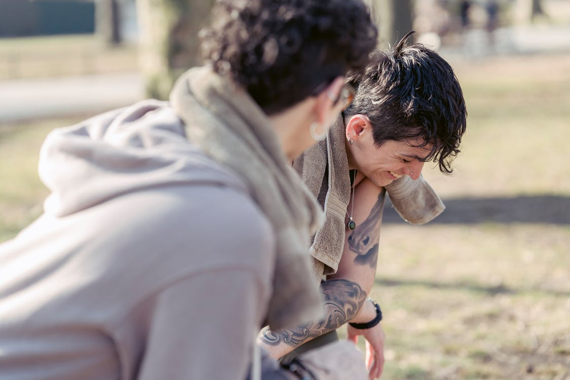Androgynous woman laughing near friend in park