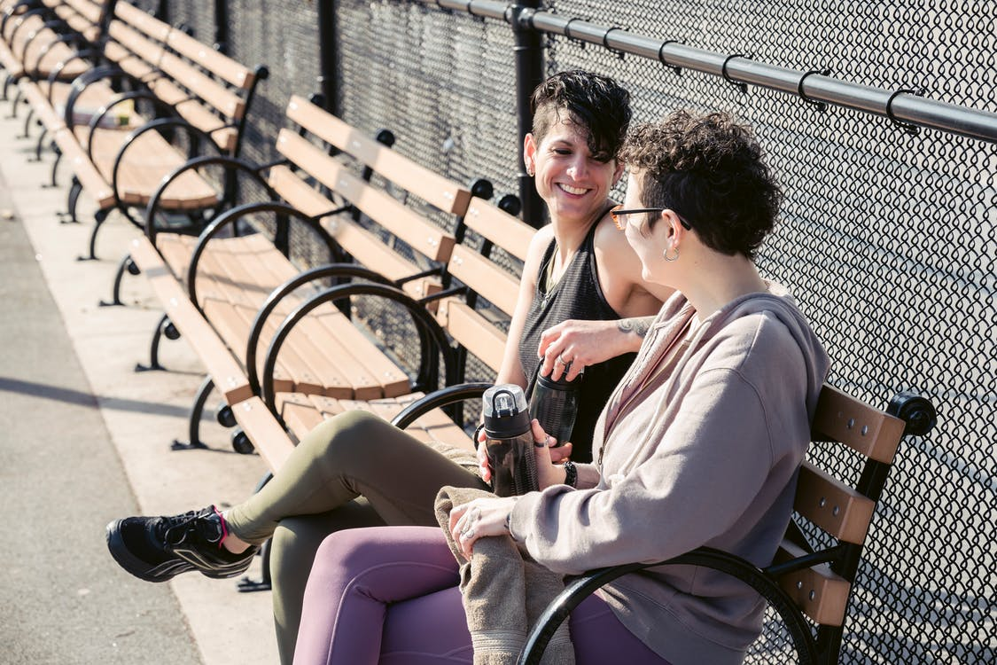 Young smiling women resting on bench