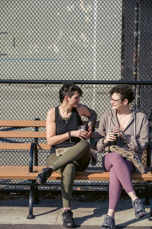 Full body of sportswomen chatting and smiling while relaxing on bench with bottles of water in hands in daylight