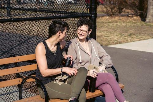 Happy sportswomen speaking on bench after training in park