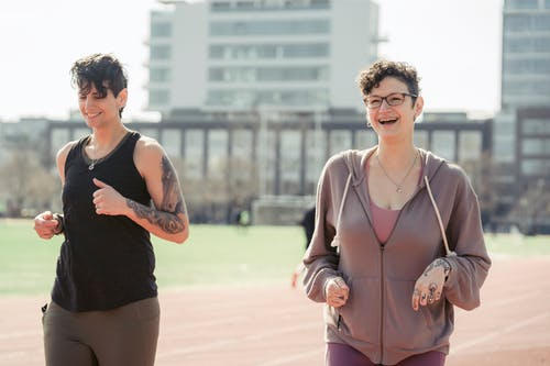 Positive young women running on sports ground in city