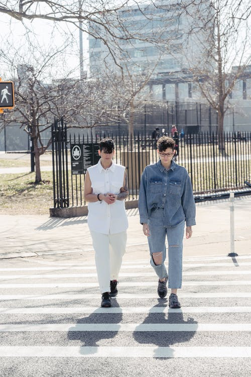 Full length of young trendy female friends with dark short hair in stylish outfits crossing asphalt road during walk in city on sunny day