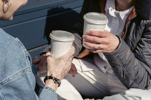 Anonymous ladies drinking takeaway coffee on bench in sunlight