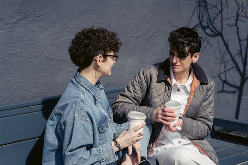 Delighted young women chatting and drinking coffee on bench