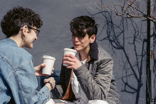 Cheerful young trendy female best friends with short hair in casual clothes smiling while drinking takeaway coffee and gossiping on bench on sunny day