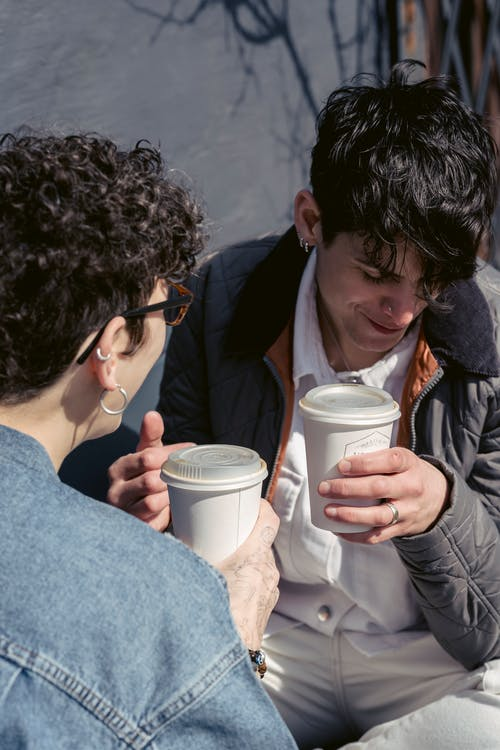 Young positive androgynous woman with short dark hair smiling and drinking coffee to go while spending time with anonymous female friend on street