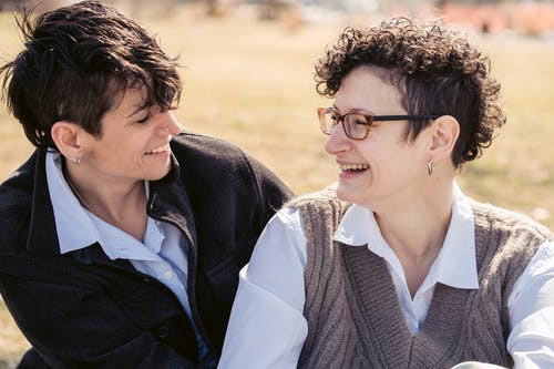 Joyful young lesbian couple laughing and hugging on lawn in park