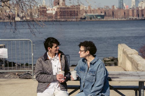 Young female friends chatting on waterfront during coffee break