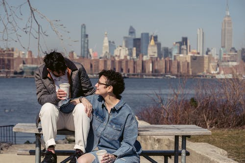 Trendy young lesbian couple smiling and drinking takeaway coffee while chilling on wooden bench at riverside in modern city