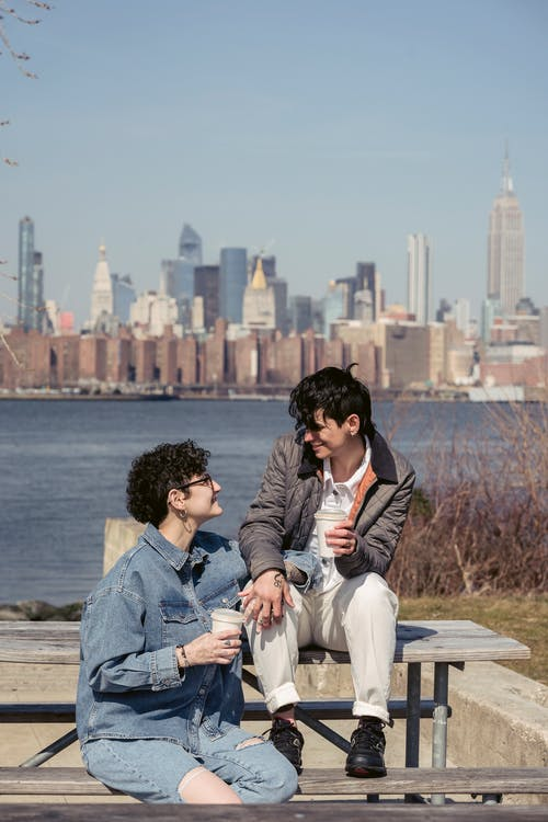 Happy young lesbians holding hands and drinking coffee on river shore in city