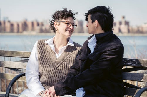 Enamored young homosexual women smiling and looking at each other while sitting on wooden bench holding hands on river embankment on sunny day