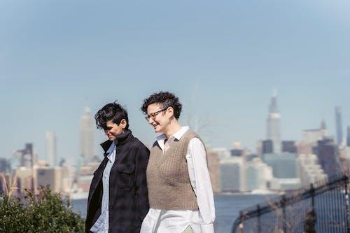 Smiling girlfriends talking on embankment in town