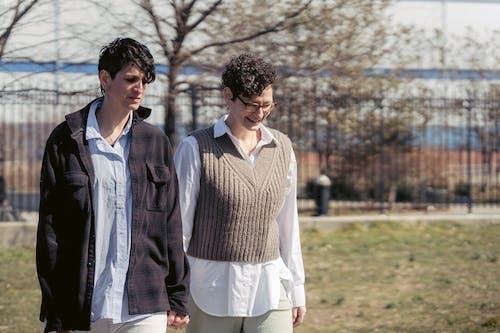 Positive androgynous friends walking on urban street