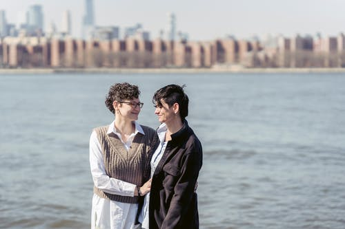 Positive women with dark short hair smiling and supporting each other on blurred background of river with embankment with buildings