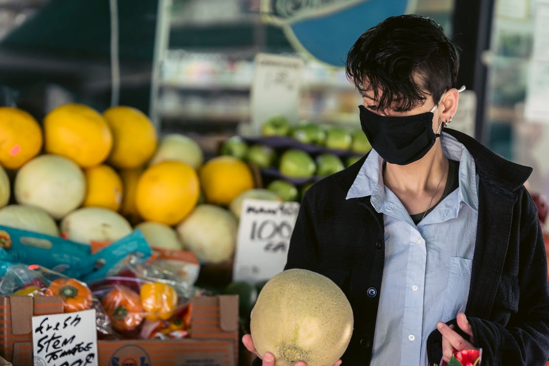 Pensive female in protective mask choosing fruits in market
