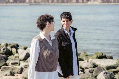 Enamored young lesbian couple with short dark hair in casual outfits smiling and looking at each other while holding hands and strolling alone stony river shore on sunny day in city