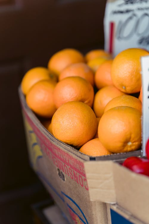 Box with heap of fresh oranges in street food market