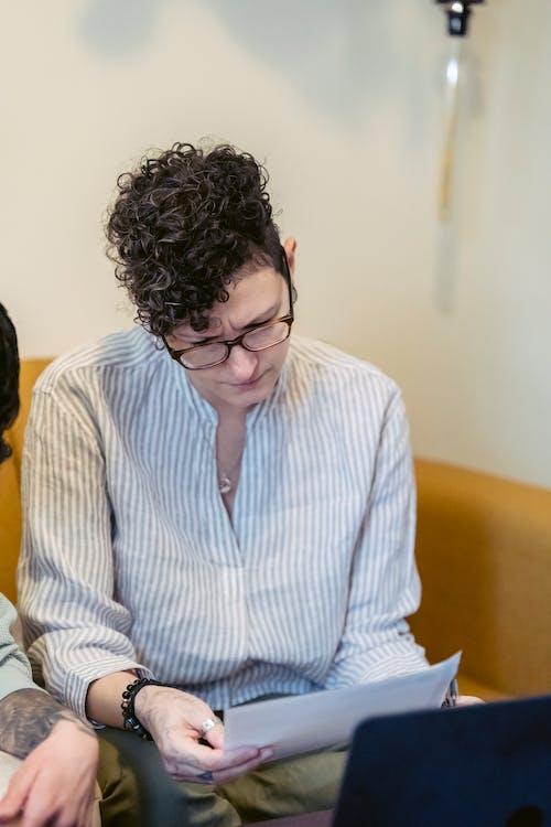 Serious young female entrepreneur reading contract near crop partner