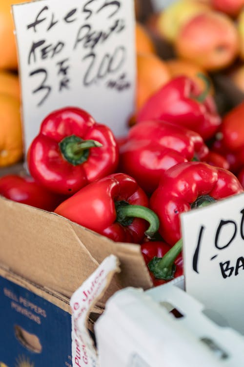 Appetizing healthy bell peppers in cardboard containers in market