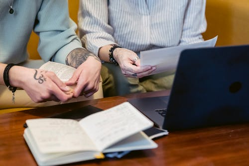 Crop unrecognizable coworkers reading reports at table with netbook
