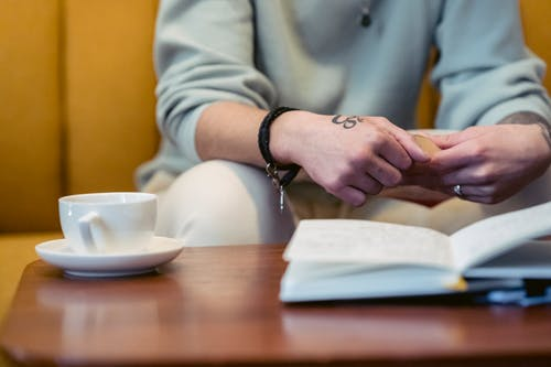 Crop anonymous tattooed person in casual clothes reading interesting book while sitting on comfortable sofa with cup of coffee