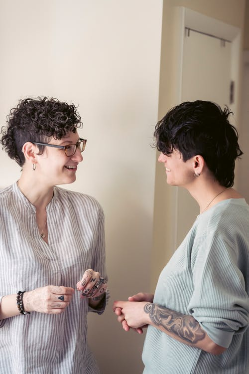 Cheerful young female best friends with dark short hair in casual outfits smiling and looking at camera while chatting at home