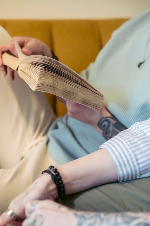 Crop anonymous tattooed person in casual clothes reading interesting novel while relaxing on sofa with faceless partner