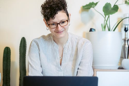 Excited young woman working remotely on netbook at home