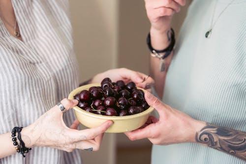 Crop women eating bowl of healthy ripe cherries