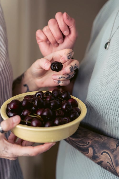 Crop anonymous couple with tattoos on arms in casual clothes eating bowl of appetizing ripe cherries at home