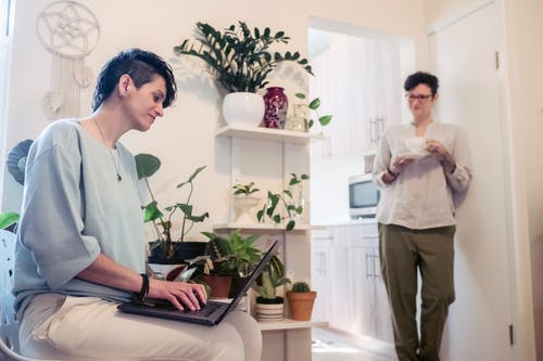 Young woman with short hair standing near wall with cup of coffee and communicating with female friend working remotely on laptop at home