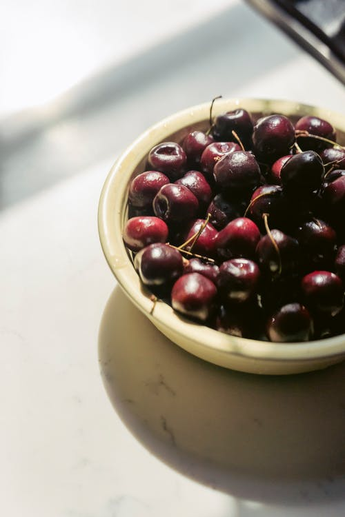 Bowl of fresh healthy ripe cherries served on table