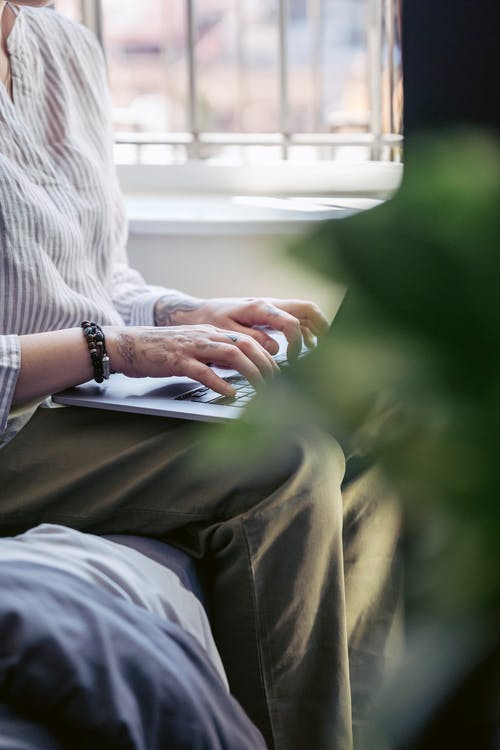 Crop faceless female freelancer in casual clothes sitting on comfortable sofa and typing on netbook while working distantly in modern apartment