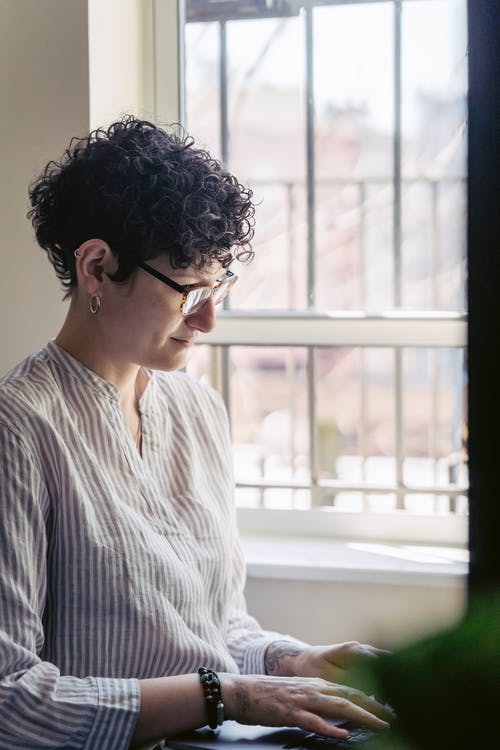 Focused female remote employee in eyeglasses and striped shirt working on netbook against window in house