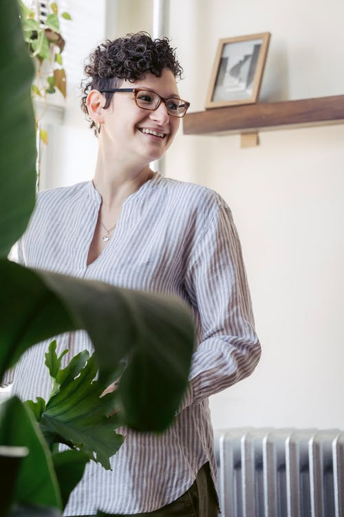 Cheerful woman against plants in house room