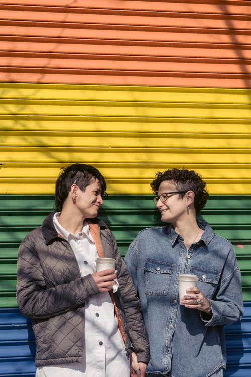 Content loving homosexual women with takeaway beverages looking at each other while standing on colorful background with LGBT rainbow flag