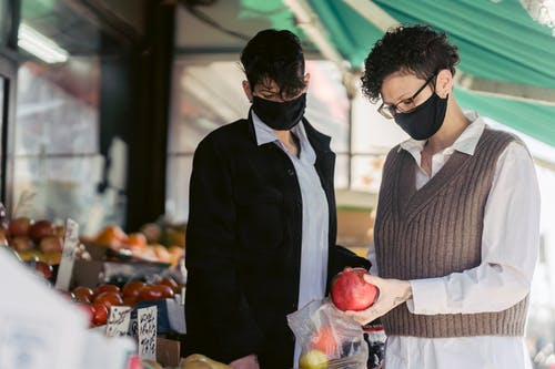 Concentrated young female friends in casual clothes and medical masks choosing fruits in local street food market on sunny day during coronavirus pandemic