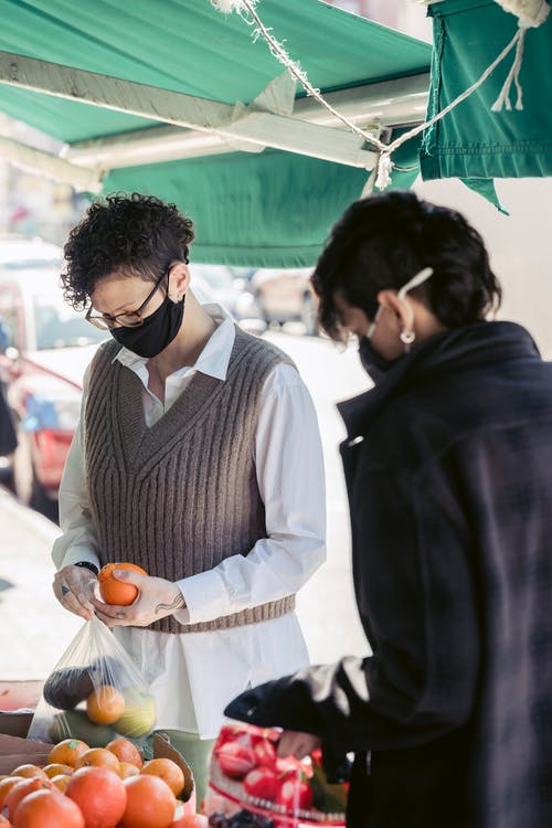 Female friends purchasing fruits and veggies in street food market